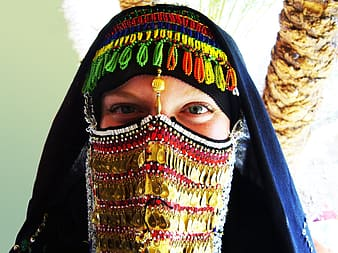 Woman covered her face with sequined mask and headdress
