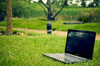 Turned off black laptop computer on green grass field