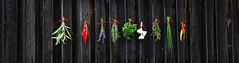 Green and purple flowers on brown wooden fence
