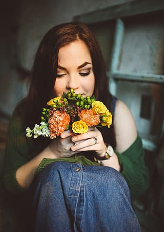 Closeup photography of woman smelling bouquet of flowers