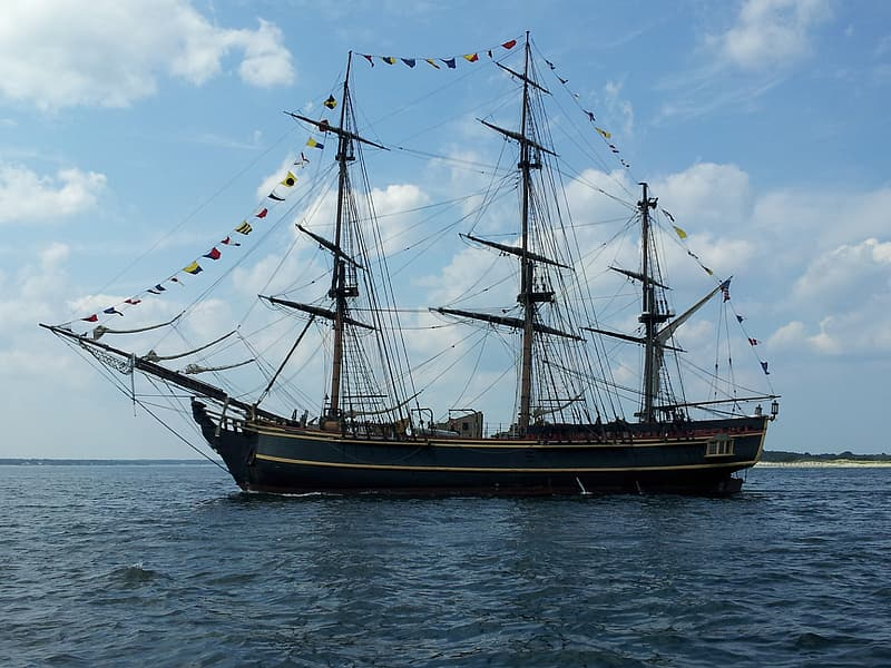 White and blue galleon ship on body of water under white clouds during daytime