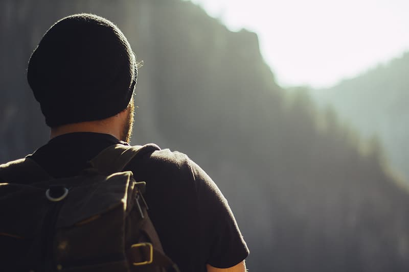 Man in black t-shirt, black beanie, and brown backpack