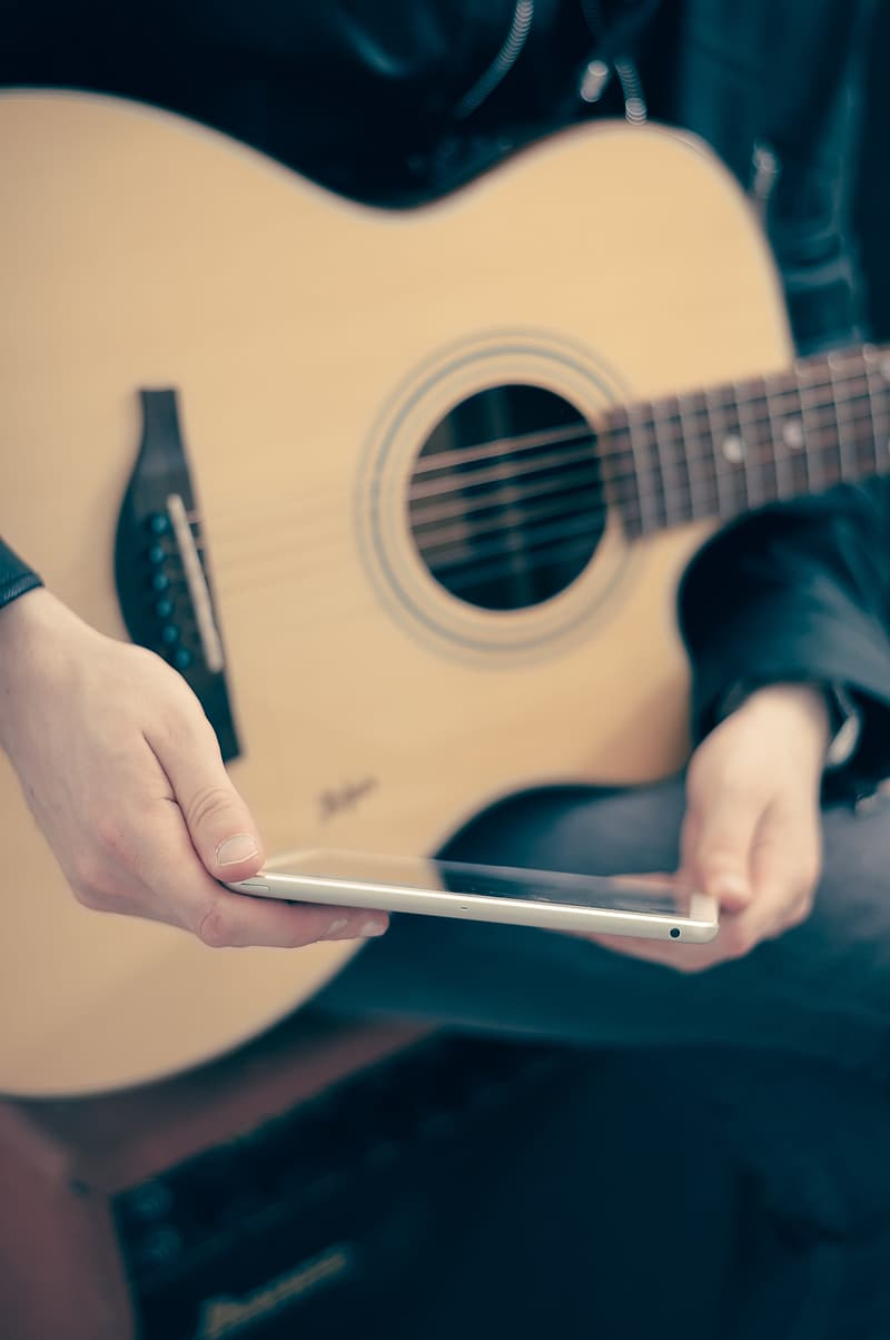 Person holding white pen and brown acoustic guitar