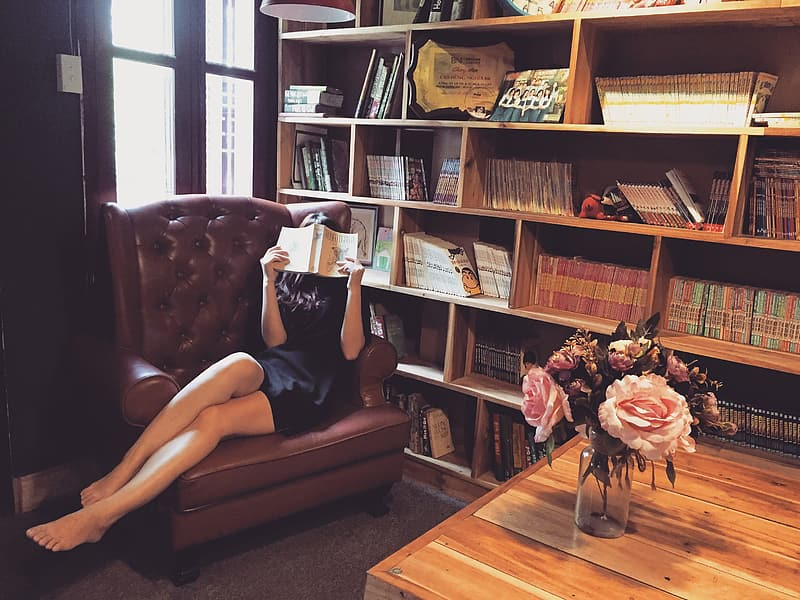 Woman wearing black mini dress reading a book at the library