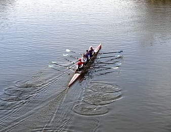 Four persons riding boat on body of water