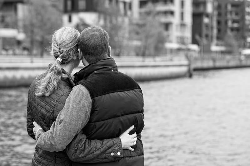 Man and woman hugging each other in grayscale photo