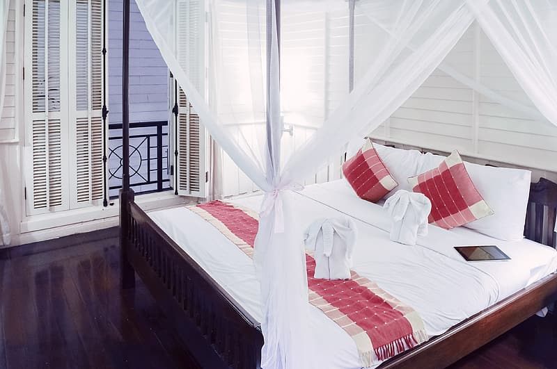 Brown wooden canopy bed with white and red comforter