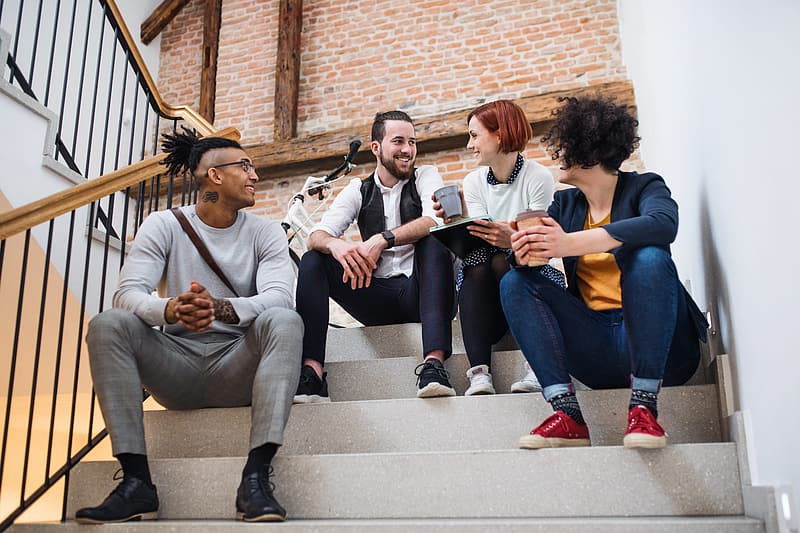 3 women and 2 men sitting on brown brick wall during daytime