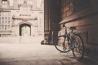 Photography of gray cruiser bicycle beside brown concrete wall
