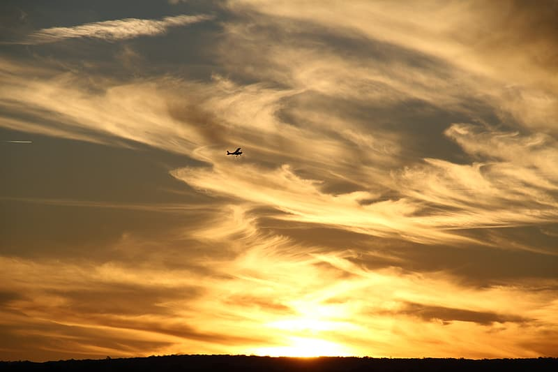 Silhouette of airplane flying over the clouds during sunset