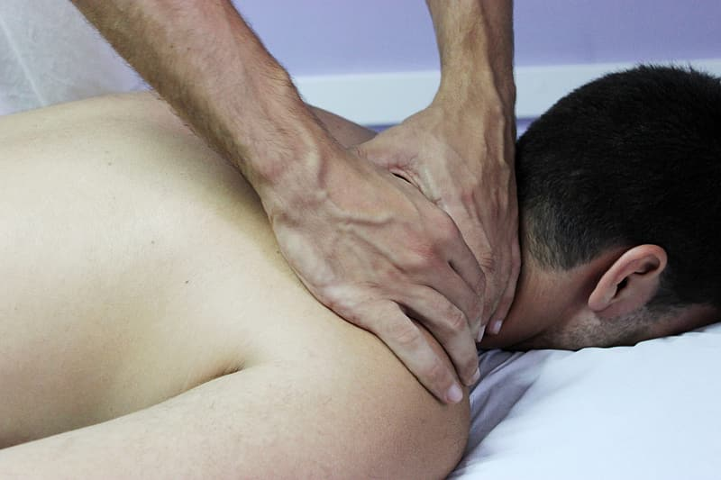 Person lying on white bed while having massage