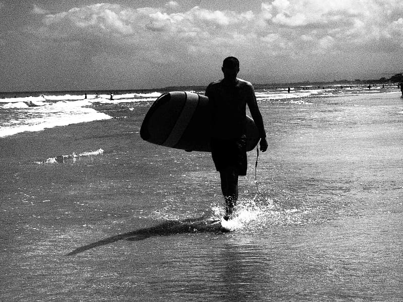 Man in black wet suit carrying surfboard walking on beach during daytime