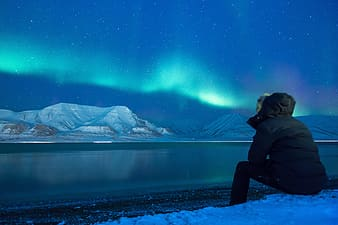 Person wearing black ski jacket sitting in front of body of water with distance at snowy hills under dark sky with Aurora borealis