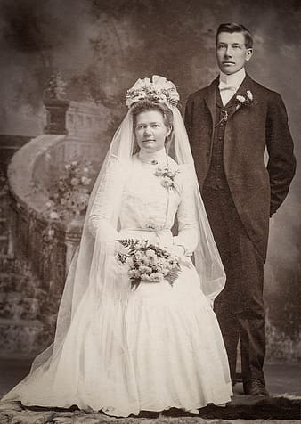Woman wearing wedding gown beside man wearing suit