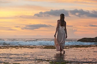 Woman in white dress walking on body of water