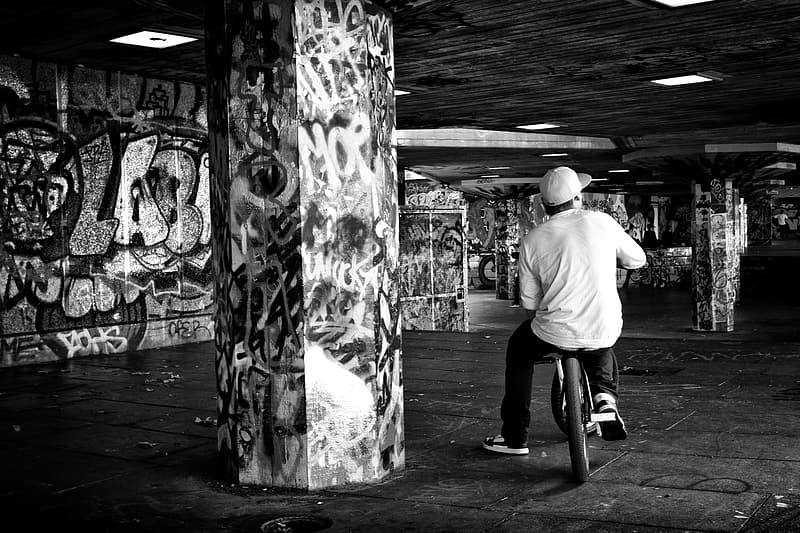 Monochrome shot of a youth sitting oh his BMX bike on the Southbank in London
