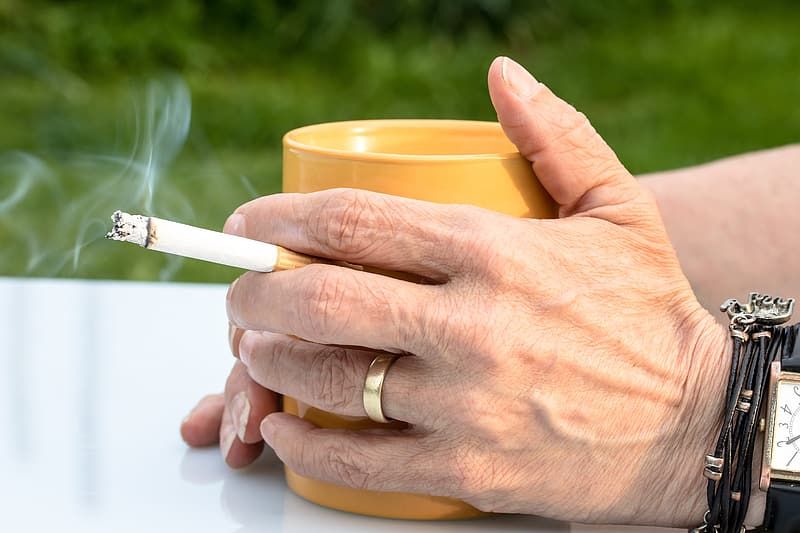 Person holding cigarette stick and yellow plastic cup