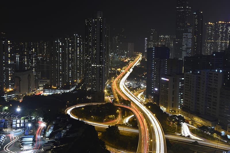 Time lapse photography of road near buildings during night time