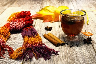 Knitted scarf beside dried leaf and shot glass on wooden surface