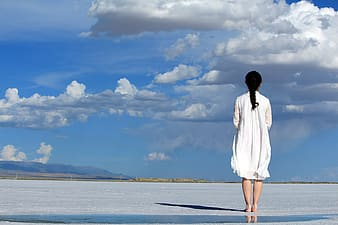 Woman wearing white dress while standing on flat surface