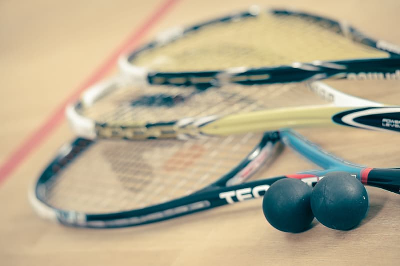 Three tennis rackets and two balls