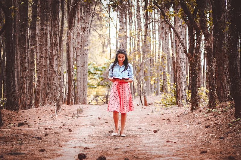 Woman standing on forest during daytime
