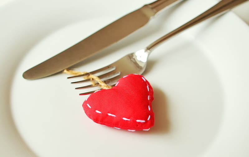 Stainless steel fork and knife on white ceramic plate