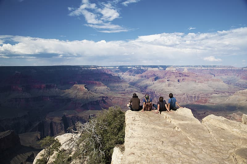 Four men sitting on top of hill