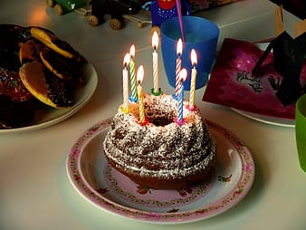 Round birthday cake on top white table with candles on top