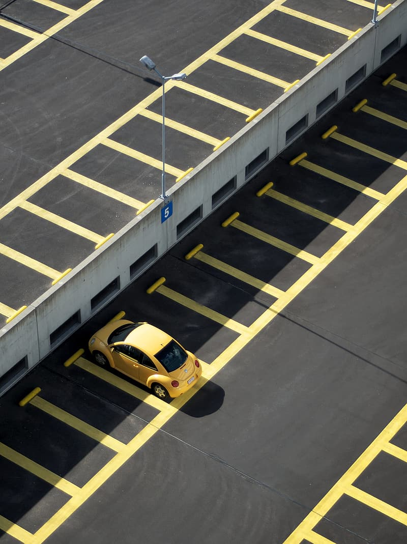 Yellow coupe on parking lot during daytime