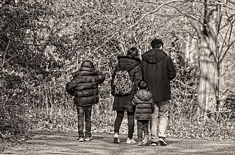Grayscale photo of family walking o