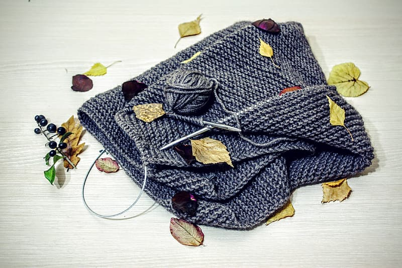 Gray knitted bag on brown wooden surface