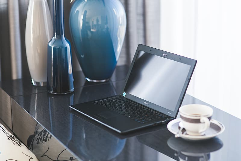 Black laptop computer turned off near coffee
