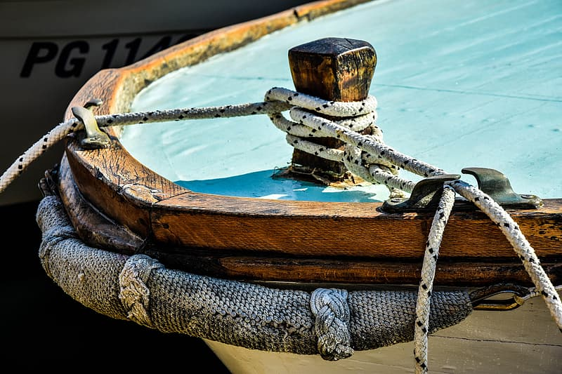 White and brown boat with gray rope parked at daytime