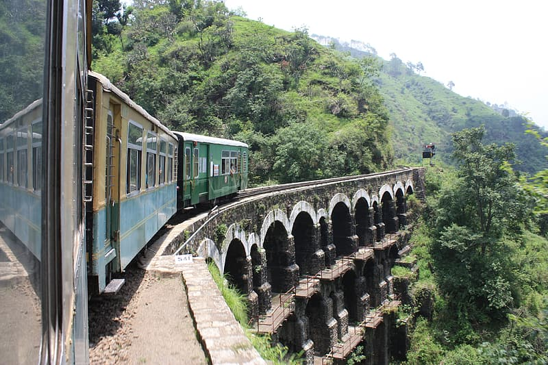 Green train passing on brown arch bridge
