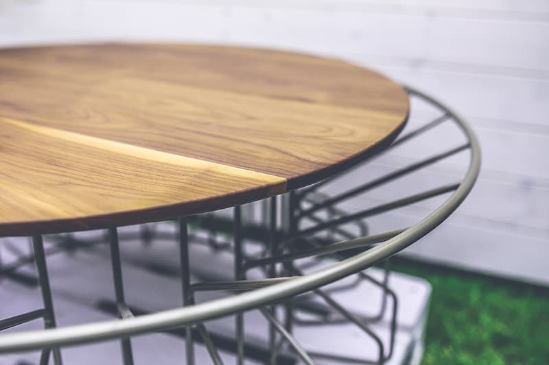 Round brown wooden board on gray metal stand