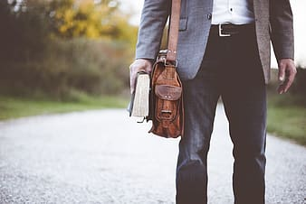 Man with bag holding book