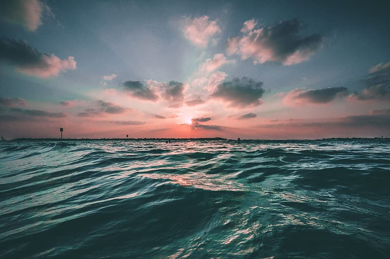 Body of water under cloudy sky during sunset