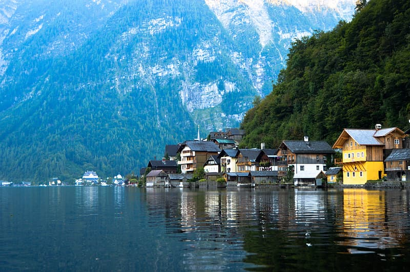 Houses near body of water and mountains