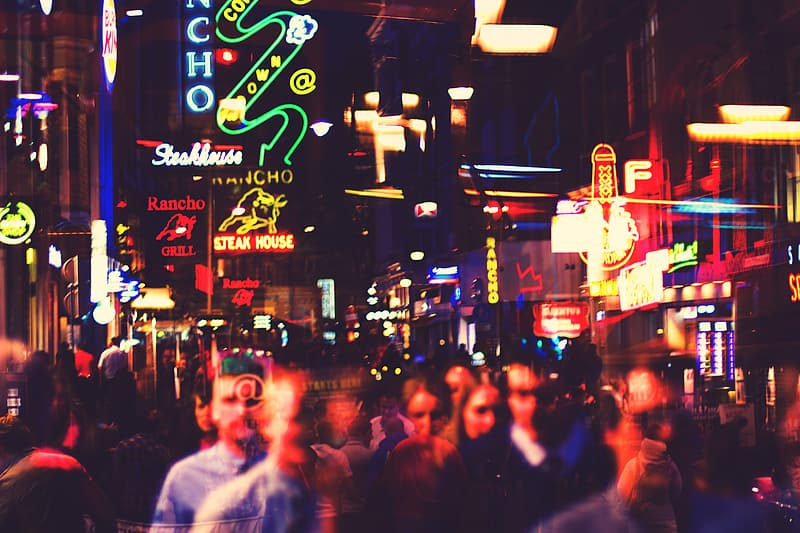 Time lapse photography of crowd of people walking near lighted buildings