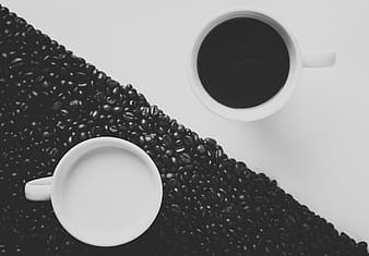 Two white mugs with black and white liquid