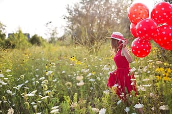 Woman in red sleeveless dress holding red balloons walking on green plants during daytime