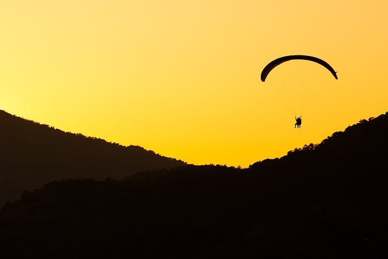 Silhouette of person parachuting near valley during sunset