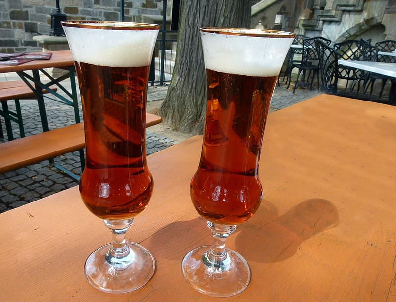 Two clear glass footed cups with red liquid on table