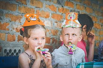 Girl and boy wearing animal themed party hats