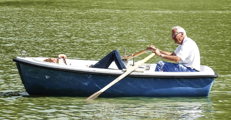 Man in white polo shirt in blue boat holding paddle during daytime