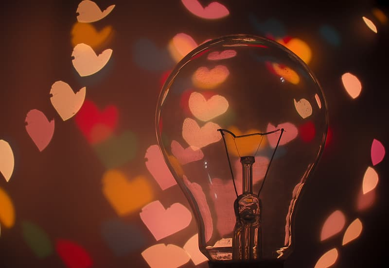 Closeup photography of clear glass bulb with heart backgrounds
