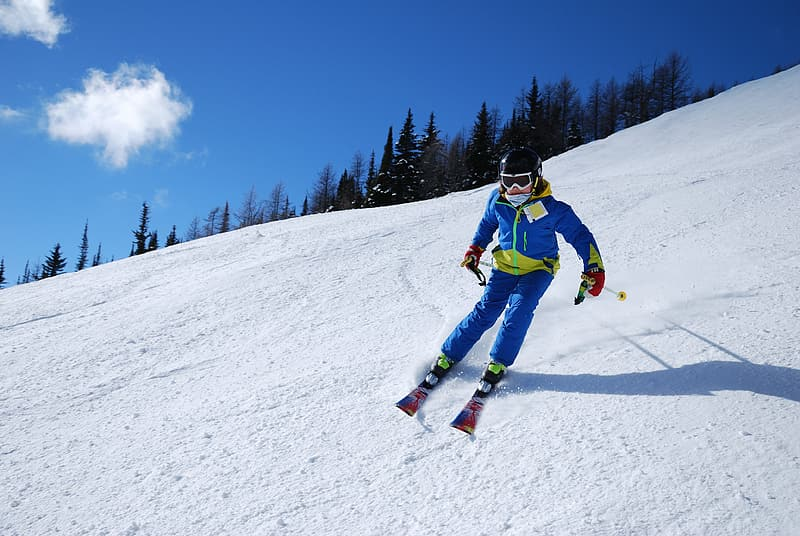 Man in blue jacket and blue pants on snow covered ground during daytime