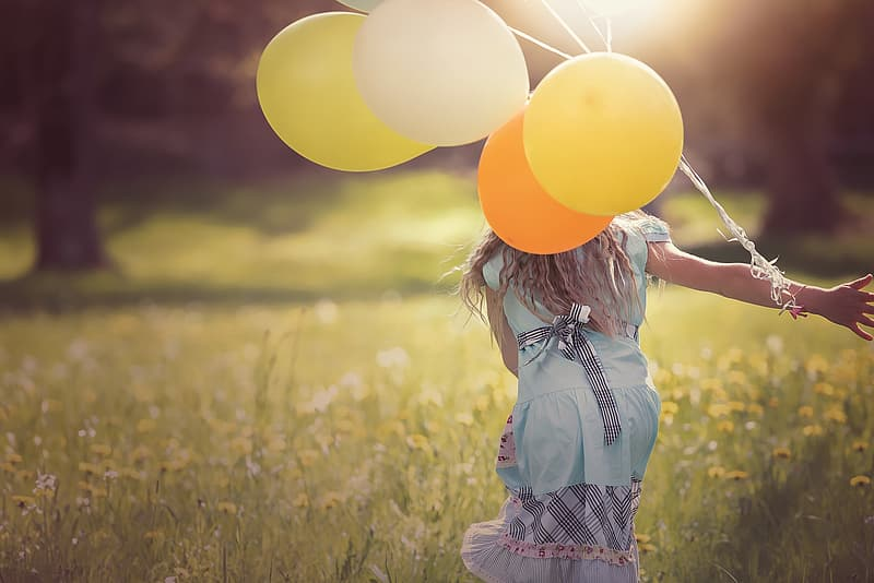 Selective focus photography of girl in blue dress holding yellow balloons while playing on grass field