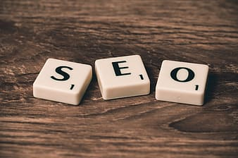 Three SEO scrabble pieces on brown wooden surface